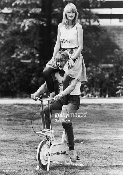 English racing driver James Hunt poses on an exercise bicycle with ex-girlfriend Jane Birbeck on his shoulders to publicise the opening of their...
