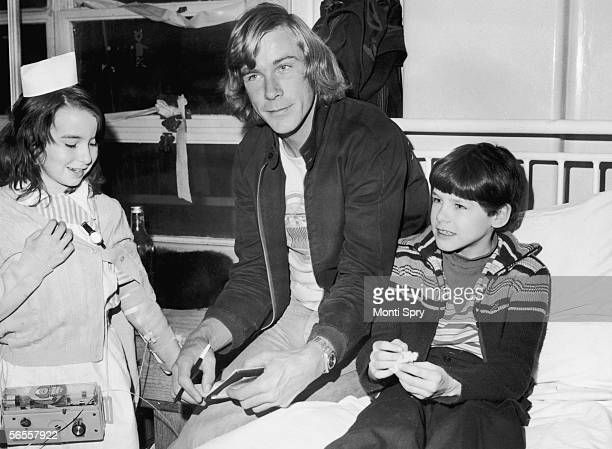 English racing driver James Hunt with patients Lynn Boyce and Tyrone Wyman during a visit to Great Ormond Street Children's Hospital London 3rd...