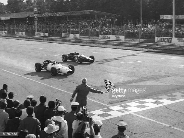 English racing driver John Surtees takes the chequered flag to win the Italian Grand Prix at Monza in a Honda RA300 10th September 1967 Jack Brabham...