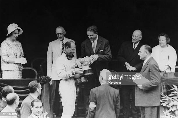 English racing driver Stirling Moss receives his trophy after winning the Monaco Grand Prix at Monte Carlo, 14th May 1961.