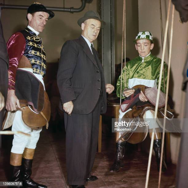 English racing jockey Manny Mercer , wearing green silks, weighing-in in the weighing room at a racecourse in England in November 1956.