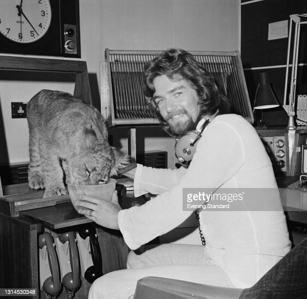 English Radio 1 DJ Noel Edmonds with Tiddles the lion cub, in his recording studio at Broadcasting House, London, UK, 30th August 1973.