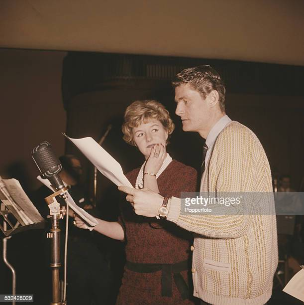 English radio and television presenter Pete Murray pictured with actress Joan Sims in a recording studio in 1963