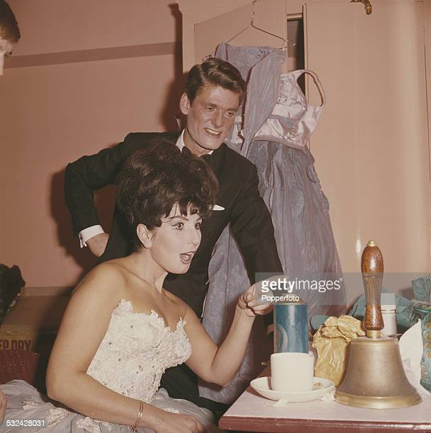 English radio and television presenter Pete Murray pictured with singer Alma Cogan backstage in 1963