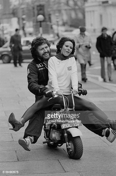 English radio broadcaster and DJ Dave Lee Travis pictured riding a mini bike with actress Judy Carne in Lower Regent Street London on 6th January 1981