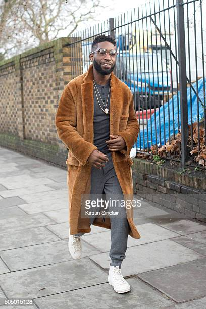 English rapper Tinie Tempeh wears Burberry coat and trousers on day 4 of London Collections Men on Januay 11 2016 in London England Tinie Tempeh