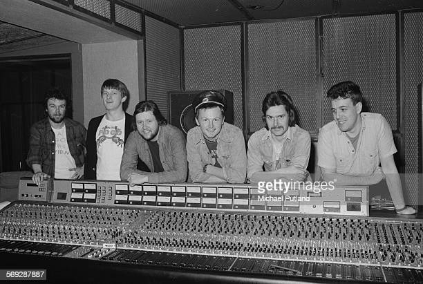English record producer Mike Batt with pub rock group The Kursaal Flyers in a recording studio March 1976 The group are recording their third album...