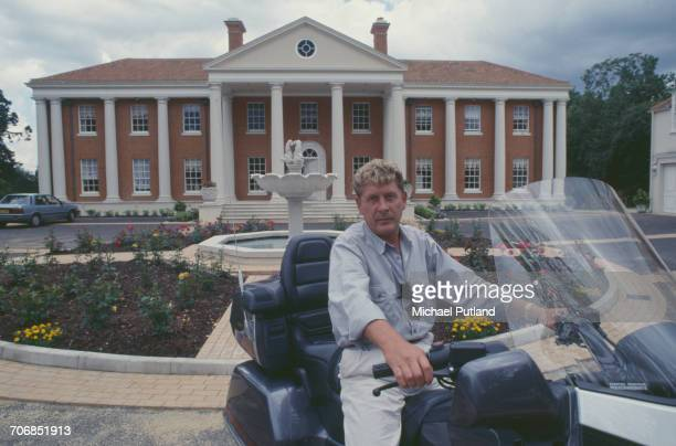English record producer music executive and founder of Rak Records Mickie Most posed on a Honda Gold Wing motorcycle outside his house in Totteridge...