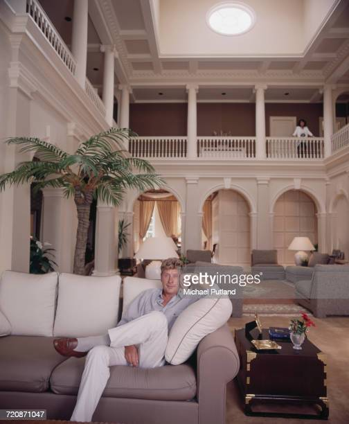 English record producer music executive and founder of Rak Records Mickie Most posed sitting on a sofa in his house in Totteridge North London in 1988