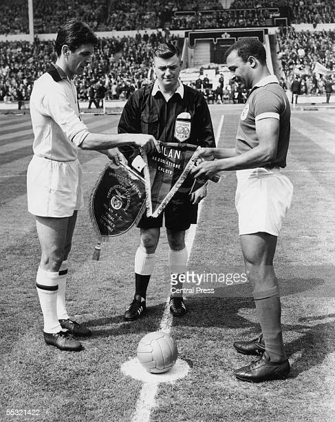 English referee A Holland watches as AC Milan captain Cesare Maldini and the Benfica captain exchange pennants before the European Cup final at...