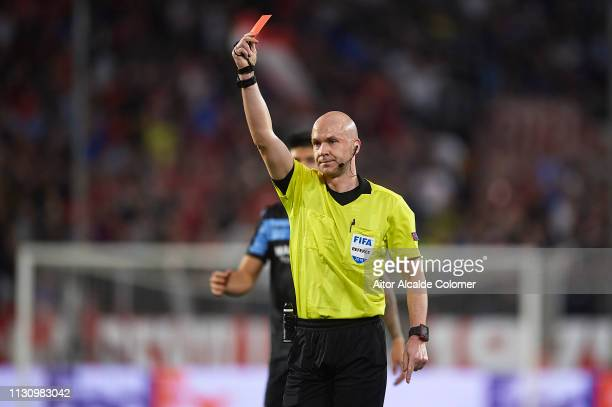 English referee Anthony Taylor shows a red card to Adam Marusic of SS Lazio during the UEFA Europa League Round of 32 Second Leg match between...