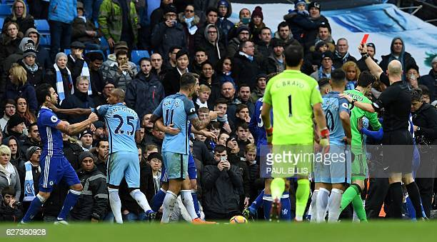 English referee Anthony Taylor shows a red card to Manchester City's Brazilian midfielder Fernandinho as he grabs Chelsea's Spanish midfielder Cesc...