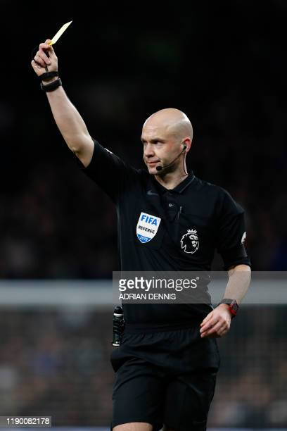 English referee Anthony Taylor shows a yellow card during the English Premier League football match between Tottenham Hotspur and Chelsea at...