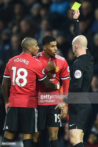 English referee Anthony Taylor shows a yellow card to Manchester United's English striker Marcus Rashford after a clash with West Bromwich Albion's...