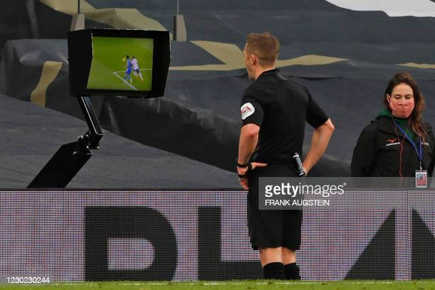 English referee Craig Pawson checks the touchline screen before giving a penalty to Leicester for a foul by Tottenham Hotspur's Ivorian defender...