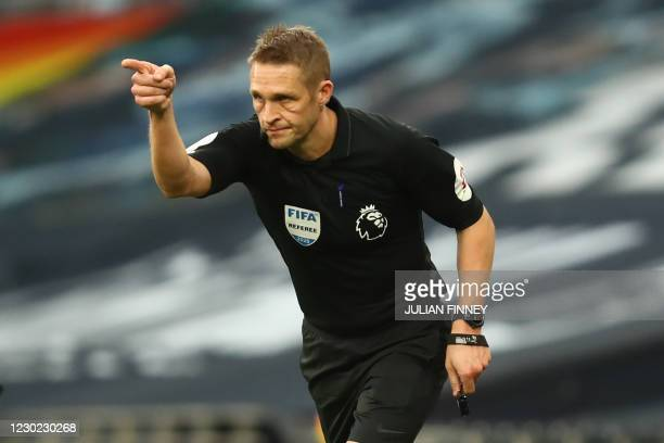 English referee Craig Pawson indicates a penalty after checking the touchline screen to study a foul by Tottenham Hotspur's Ivorian defender Serge...