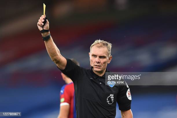 English referee Graham Scott shows a yellow card to Manchester United's English defender Aaron Wan-Bissaka during the English Premier League football...