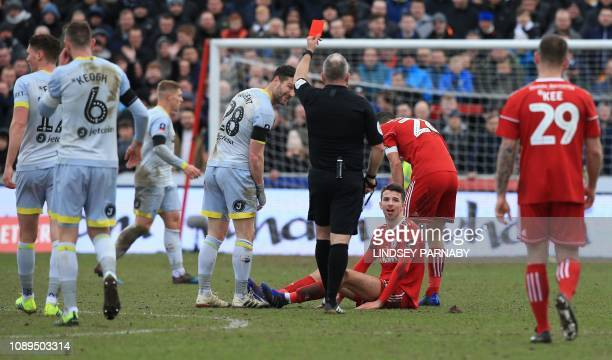 English referee Jonathan Moss shows a red card to Accrington Stanley's English midfielder Daniel Barlaser for his foul on Derby County's English...