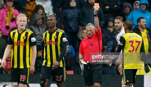 English referee Jonathan Moss shows a red card to Watford's Zaireborn Belgian defender Christian Kabasele during the English Premier League football...