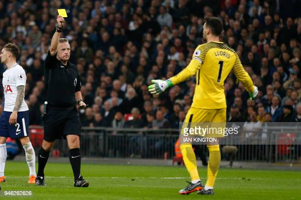 English referee Jonathan Moss shows a yellow card to Tottenham Hotspur's French goalkeeper Hugo Lloris after he brings down Manchester City's English...