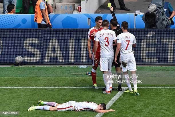 English referee Mark Clattenburg gives Switzerland's defender Fabian Schaer a yellow card after a tackle on Poland's forward Robert Lewandowski...