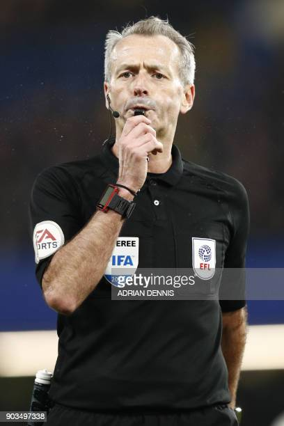 English referee Martin Atkinson blows his whistle during the English League Cup semifinal first leg football match between Chelsea and Arsenal at...