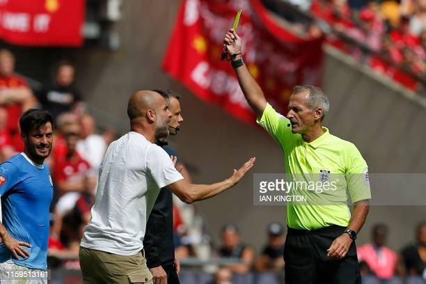 TOPSHOT English referee Martin Atkinson shows a yellow card to Manchester City's Spanish manager Pep Guardiola during the English FA Community Shield...