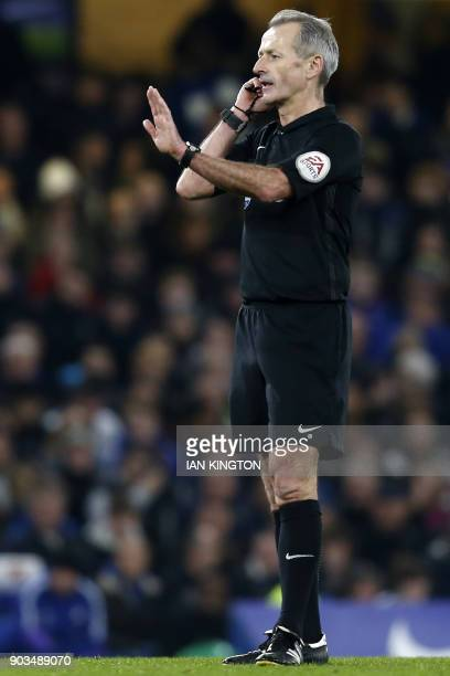 English referee Martin Atkinson stops play to consult with the Video Assistant Referee during the English League Cup semifinal first leg football...