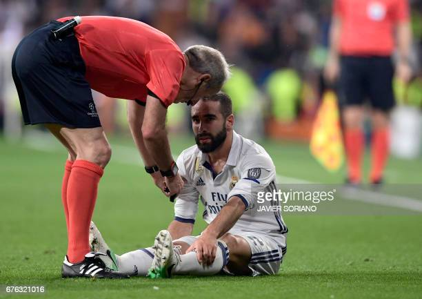 English referee Martin Atkinson talks to Real Madrid's defender Dani Carvajal during the UEFA Champions League semifinal first leg football match...