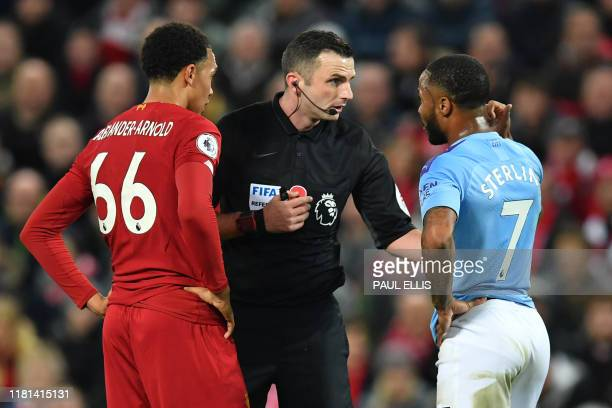English referee Michael Oliver chats with Manchester City's English midfielder Raheem Sterling and Liverpool's English defender Trent AlexanderArnold...