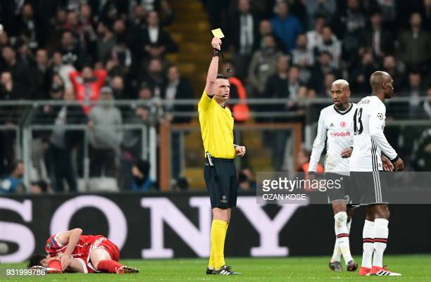 English referee Michael Oliver issues a yellow card to Besiktas midfielder Atiba Hutchinson during the second leg of the last 16 UEFA Champions...