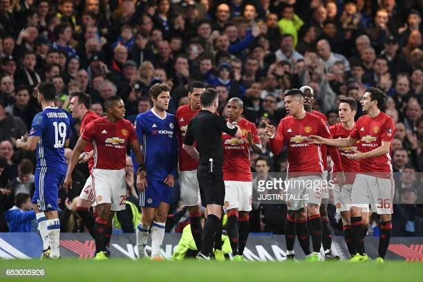 English referee Michael Oliver speaks with Manchester united players after showing a red card for a second bookable offence to Manchester United's...