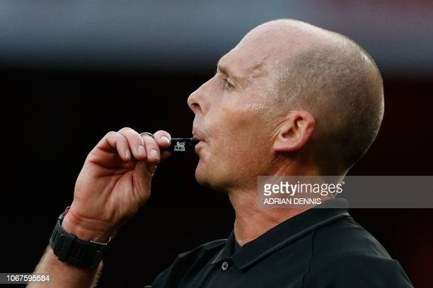 English referee Mike Dean blows his whistle during the English Premier League football match between Arsenal and Tottenham Hotspur at the Emirates...
