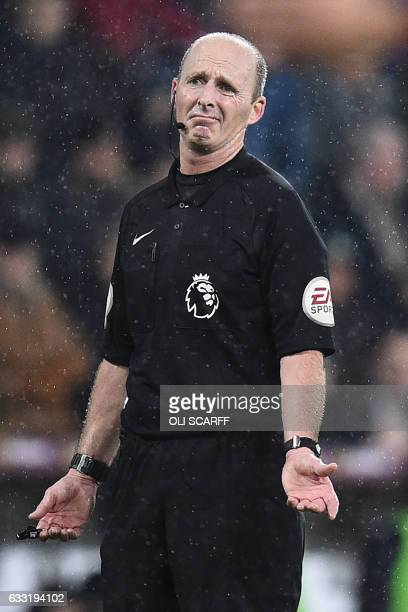 English referee Mike Dean gestures as Burnley make a claim for a penalty during the English Premier League football match between Burnley and...
