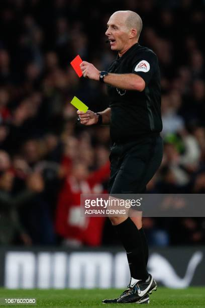 English referee Mike Dean gets out a red card to show to Tottenham Hotspur's Belgian defender Jan Vertonghen during the English Premier League...