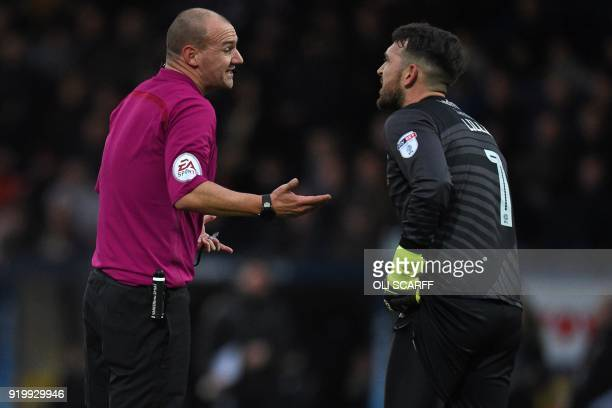 English referee Robert Madley talks with Rochdale's English goalkeeper Josh Lillis during the English FA Cup fifth round football match between...
