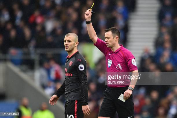 English referee Stuart Attwell shows a yellow card to Arsenal's English midfielder Jack Wilshere for a foul during the English Premier League...