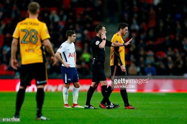 English referee Stuart Attwell stops play to consult his VAR about a possible penalty incident during the English FA Cup fourth round replay football...