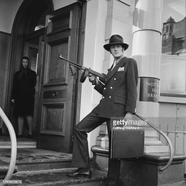 English retail entrepreneur Harold Tillman arrives at a Notting Hill bank dressed as an American gangster, complete with prop Tommy gun, London, UK,...