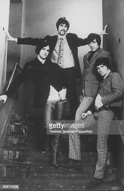 Music group The Kinks posing on the flight of stairs wearing checkered pants and jackets flowered ties and boots extending pass the thighs