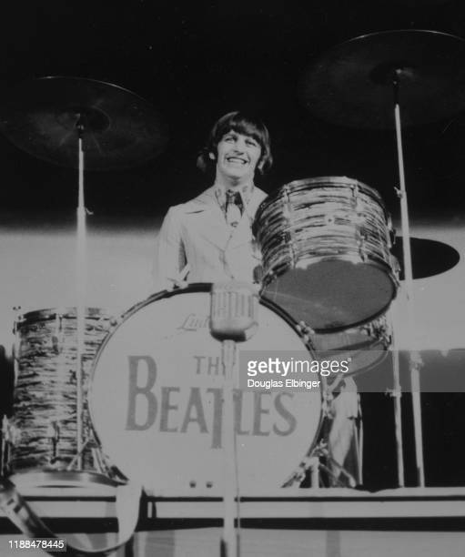 English Rock and Pop musicians Ringo Starr , of the group the Beatles, plays drums as he performs onstage at Olympia Stadium, Detroit, Michigan,...