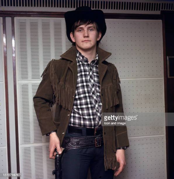 English rock and pop singer Wayne Fontana poses for a portrait with his hat and gun circa 1966 in London, England.
