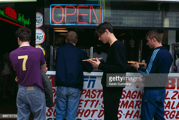 English rock band Blur queue for pizza at a snack stand circa 1995 From left to right guitarist Graham Coxon drummer Dave Rowntree bassist Alex James...
