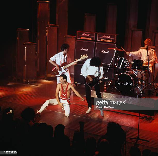 Queen bassist John Deacon singer Freddie Mercury guitarist Brian May and drummer Roger Taylor on stage during a live concert performance circa 1980