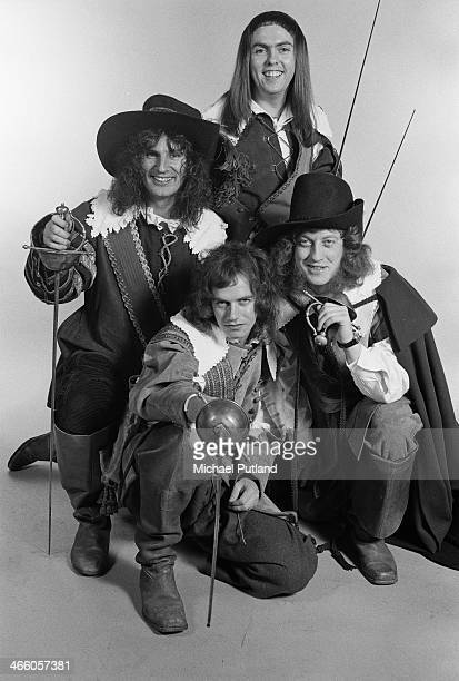 English rock group Slade posing in cavalier costumes and holding swords London 1974 Clockwise from front bassist Jim Lea drummer Don Powell guitarist...