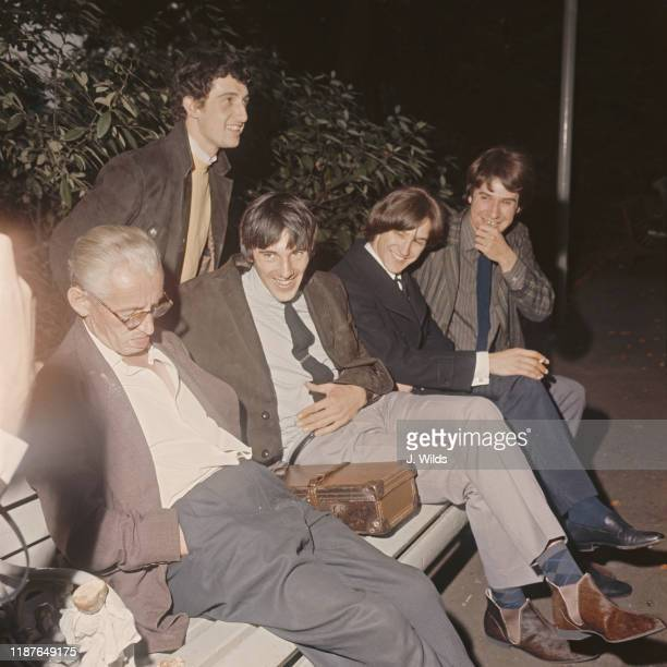 English rock group The Kinks sharing a park bench with an elderly sleeping man in Embankment Gardens London 7th September 1964 The Kinks are Pete...