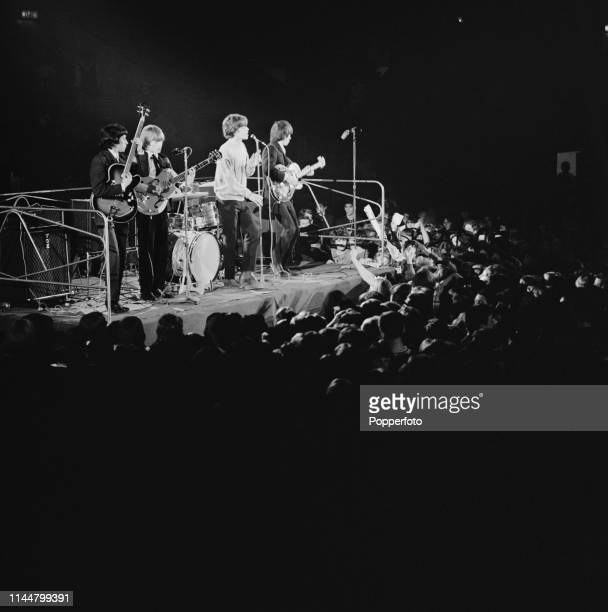 English rock group The Rolling Stones perform live on stage during Ready Steady Go's live television broadcast of the Rave Mad Mod Ball at Wembley...