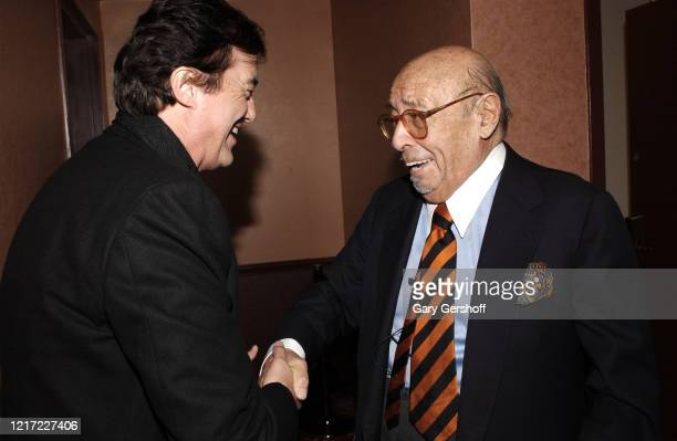English rock musician Jimmy Page , of the group Led Zeppelin, and Turkish-born American businessman, Atlantic Records president Ahmet Ertegun shake...