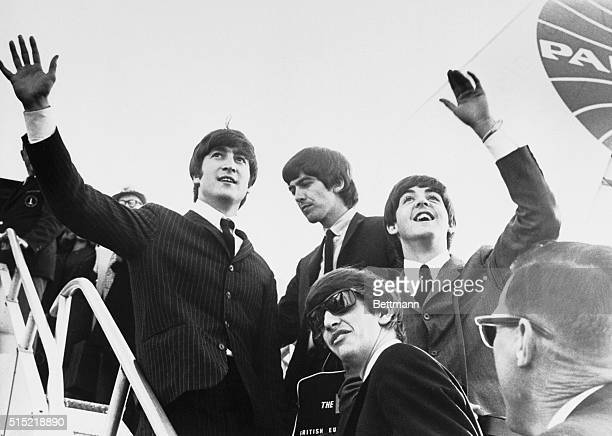 English rock 'n' roll sensations the Beatles John Lennon George Harrison Paul McCartney and Ringo Starr wave to several hundred screaming fans before...