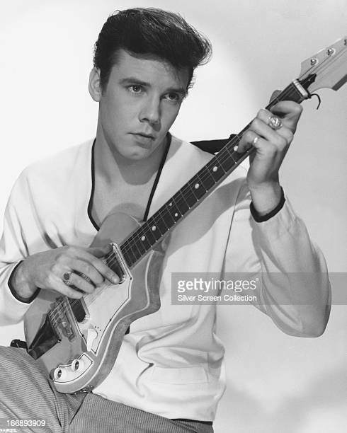 English rock 'n' roll singer Marty Wilde posing with an electric guitar circa 1960